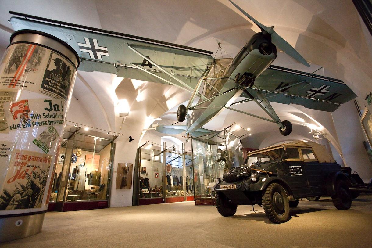 Ein Jeep und ein Flugzeug umgeben von Vitrinen und einer Litfaßsäule in der Ausstellung über die Erste Republik.