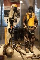 Schaufensterpuppe in Fliegeruniform mit Gasmaske, daneben eine Bombe in der Vitrine.