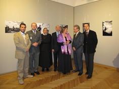 Damen und Herren, eine Nonne und ein General stehen in der Ausstellung in einer Gruppe beisammen und schauen in die Kamera.
