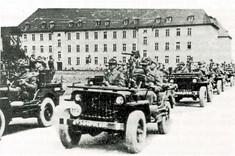 Schwarz-Weiß-Foto mehrerer Jeeps mit Soldaten.