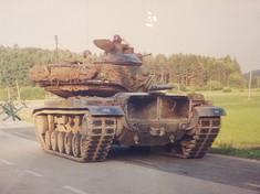 Panzer auf einer Straße, daneben Wiese.
