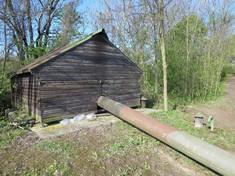 Holzhütte, aus der ein großes Rohr ragt, daneben Bäume.
