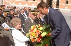 Günter Platter überreicht einer älteren Dame im Publikum sitzend unter freiem Himmel einen Blumenstraße.