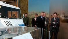Kurator zeigt einer Besuchergruppe ein UN-Fahrzeug.