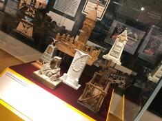 Miniaturen aus Stein und Holz in einer Vitrine.