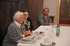 Zeitzeugin Danuta Nemling sitzt mit einer Frau und einem Mann an einem Tisch mit Zeitschriften und spricht.
