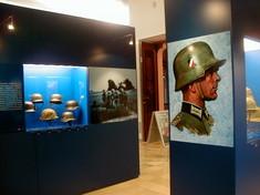 Vitrine mit verschiedenen Soldatenhelmen, davor ein Plakat mit einem Soldaten im Profil.