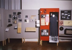 Schauwand mit kleinen gerahmten Fotografien und Zetteln, daneben ein Spind, in dem ein Damenkleid hängt.