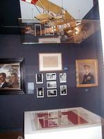 Mehrere gerahmte Fotografien und Gemälde an der Wand, ein Schaukasten und darüber an der Decke das Modell eines Militärflugzeugs.