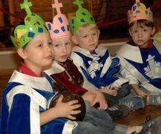 Vier Buben mit Umhängen sitzen nebeneinander und tragen Kronen aus Papier auf den Köpfen.