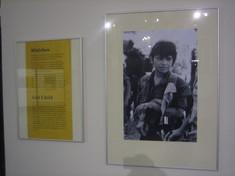 Gerahmtes Schwarz-Weiß-Foto von einem jungen Mann an der Wand neben einem gerahmten Dokument.