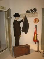 Schaufensterpuppe im Anzug mit Hut hängt eine Jacke auf eine Garderobe, neben ihr steht ein Koffer.
