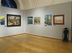 Schauwände im rechten Winkel mit zum Teil gerahmten Gemälden.