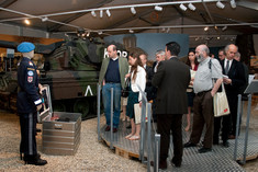 Besuchergruppe steht vor einer Schaufensterpuppe in UNO-Uniform.