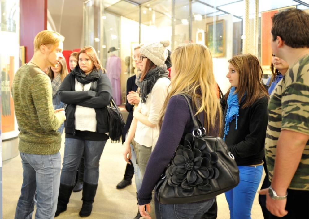 Kulturvermittler Mag. Martin Friessnegg im Gespräch mit Jugendlichen, die um ihn herum stehen.