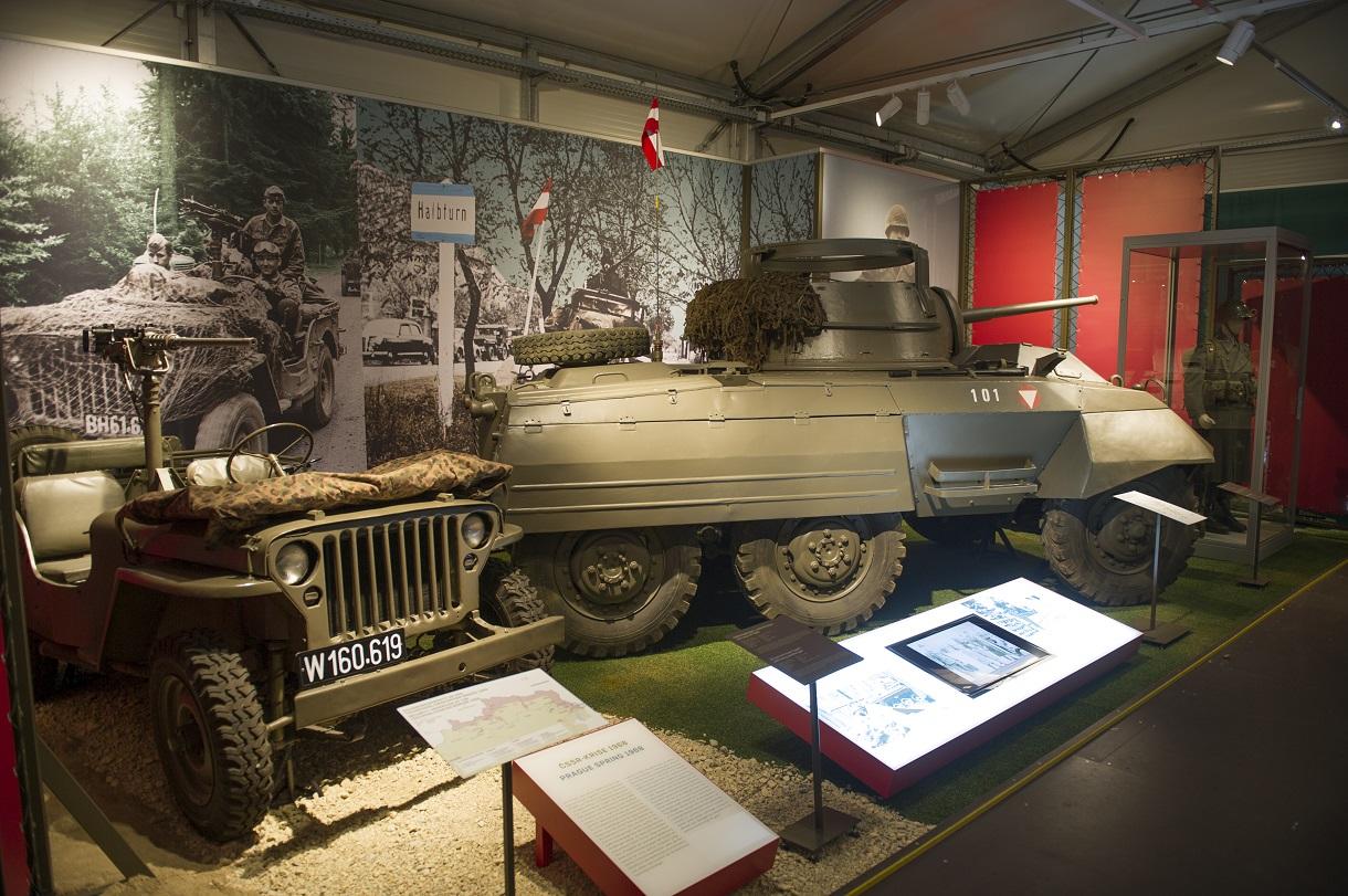Links ein Militärfahrzeug, rechts ein Panzer mit kleinen Infotafeln davor.