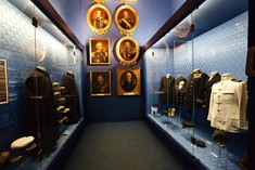 Schmaler Raum mit Schaukästen voller Uniformen links und rechts, geradeaus schön gerahmte Porträts verschiedener Marinegeneräle.