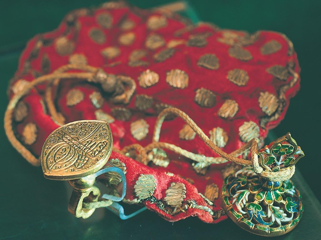 Kunstvoll gestalteter Stoffbeutel mit aufgenähten Ornamenten und Anhängern.