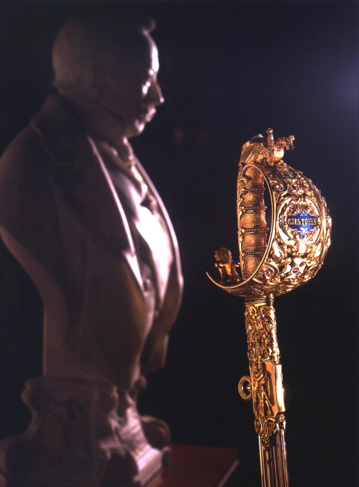 Kunstvoll verzierter Goldgriff eines Schwertes, dahinter eine Männerbüste im Profil.