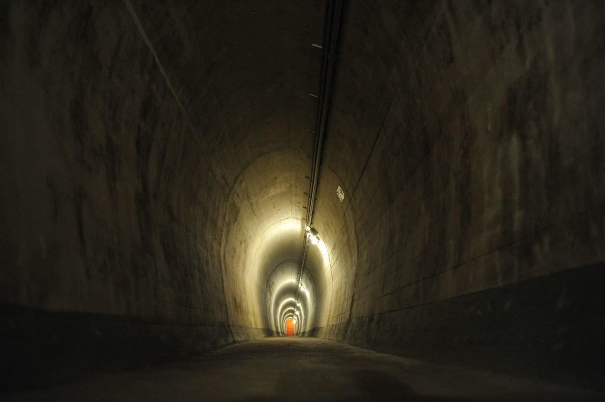 Langer Tunnel im Bunker mit Licht und einer roten Tür am Ende.
