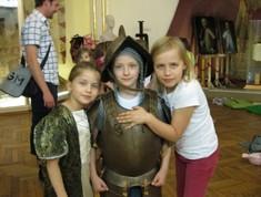 Drei junge Mädchen verkleidet als Burgfräulein und Ritter stehen nebeneinander.