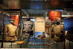 Drei Uniformen in einer Vitrine.