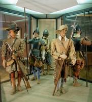 Schaufensterpuppen in historischen Uniformen in einer Vitrine.
