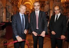 Kurator steht mit zwei Männern im Anzug vor einem roten, zerschnittenen Band.