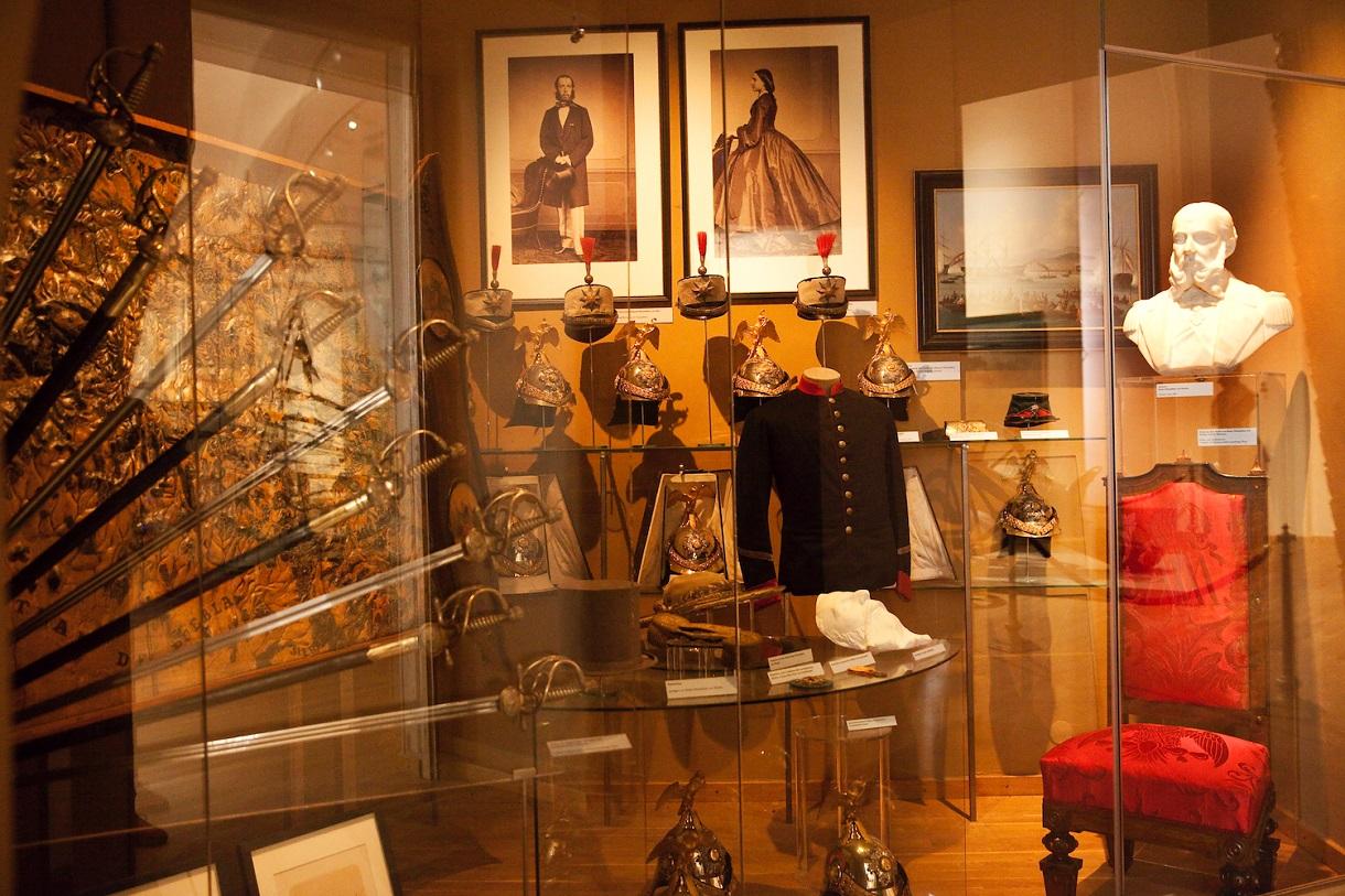 Vitrine mit Schwertern, dahinter ausgestellte Helme, Uniformjacken und Gemälde.