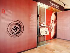 Hakenkreuz-Stempel vergrößert auf einer Schauwand, daneben ein Plakat mit Adolf Hitler im Profil