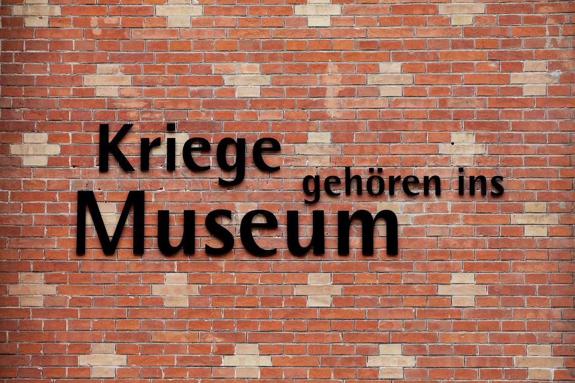 """Motto des HGM """"Kriege gehören ins Museum"""" auf der Außenfassade."""