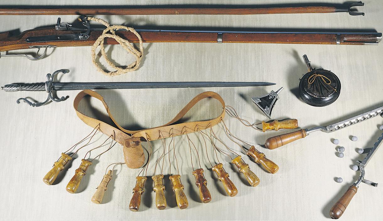 Historisches Gewehr mit Munitionsgürtel in einer Vitrine liegend.