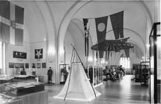 Schwarz-weiß-Foto mit Flaggen und Wimpeln in Schaukästen.