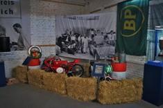 Heuballen stehen als Abgrenzung vor einer Ecke im Ausstellungsraum mit Feuerlöschern und einem Kleinmotorrad, Fahne mit BP-Logo hängt von der Wand