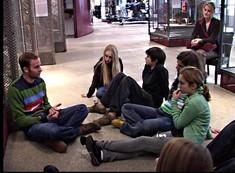 Ein junger Mann spricht mit Jugendlichen am Boden eines Ausstellungsraums sitzend.
