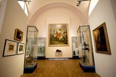 Schmaler Raum mit Gemälden an allen Wänden und Vitrinen links und rechts.