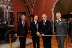 Drei Männer im Anzug und einer in Uniform stehen mit einer Schere vor einem roten Band.