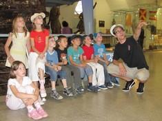 Gruppe von Kindern sitzt beisammen und hört dem Kulturvermittler zu, der auf etwas zeigt.