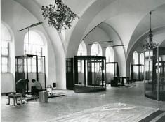 Ausstellungsraum mit Fenstern in den Torbögen auf der Seite und Vitrinen.