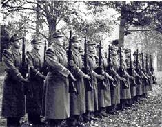 Schwarz-Weiß-Foto von einer Reihe Soldaten in Mänteln mit aufgerichteten Gewehren.