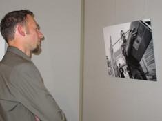 Besucher betrachtet ein Foto an der Wand.