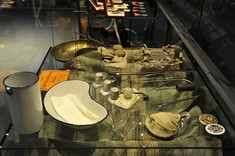 Verschiedene Ausstellungsstücke in einer Vitrine, zum Beispiel Anstecker, Fingerhüte und eine Nierenschale.