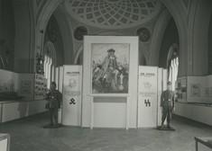 Schwarz-weiß-Foto einer Schautafel mit Gemälde, Wappen der SS und zwei Schaufensterpuppen in Uniform im Nationalsozialismus.