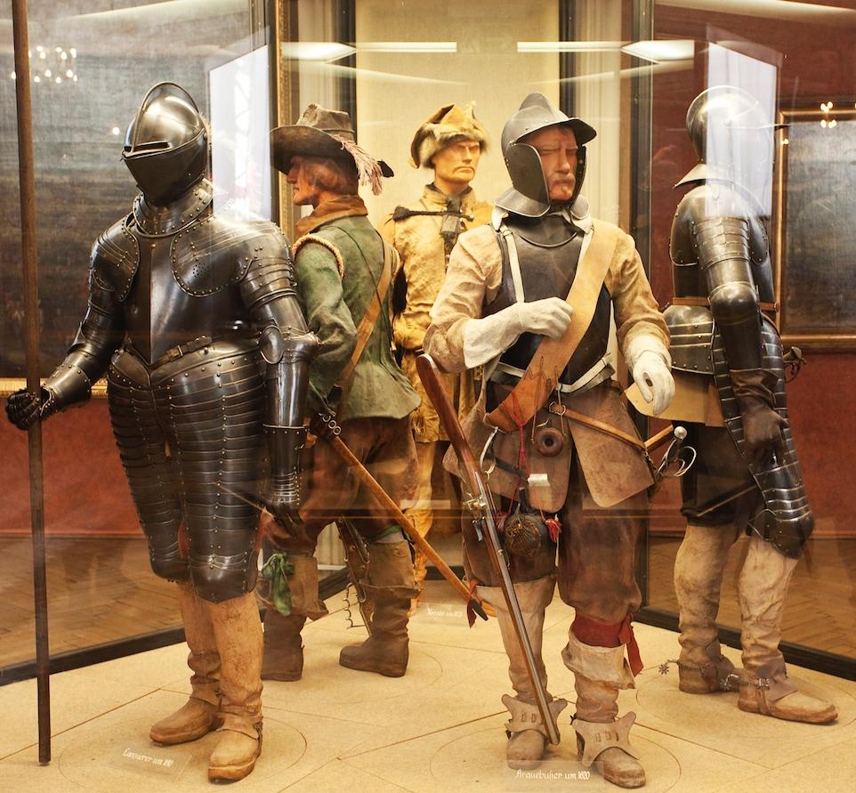Männliche Schaufensterpuppen in verschiedenen Rüstungen in einer Vitrine.