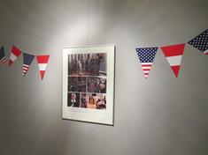 Gerahmte Fotocollage an einer Wand, links und rechts hängen Wimpel.