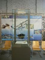 Modell eines Militärflugzeugs in einer Vitrine hängend, davor leere Stuhlreihen.