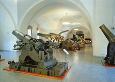 Verschiedene Geschütze und Kanonen auf Podesten im Raum verteilt.