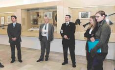 Drei Herren im Anzug und zwei Damen stehen im Halbkreis in der Ausstellung vor Schaukästen.