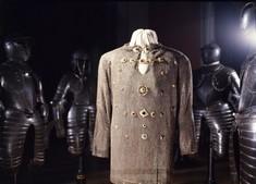 Kunstvoll verzierte und mit verscheiden großen Schmuckstücken bestickte Jacke, dahinter Rüstungen.
