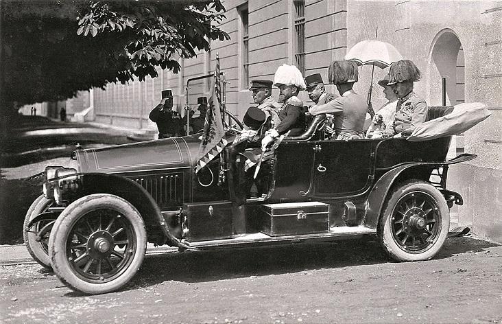 Schwarz-Weiß-Foto mit sechs Personen in einem Auto mit offenem Verdeck.